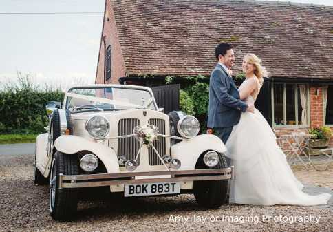 Bride and Groom posing for a photo beside the Beauford wedding car at Curradine barns.