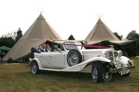 Bride and Groom sat in the Beauford wedding car with two Tepees in the background.